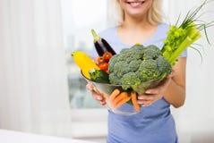 Feche acima da mulher que guarda vegetais na bacia Fotografia de Stock