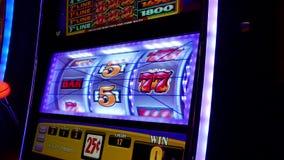 Feche acima da mulher que joga o slot machine video estoque