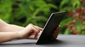 Feche acima da mulher que usa o tablet pc fora video estoque