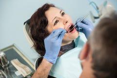 Feche acima da mulher superior bonita que tem a verificação dental acima na clínica dental dentistry foto de stock royalty free