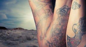 Feche acima da mulher tattooed jovens na praia Fotos de Stock