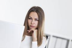 Feche acima da mulher triste no escritório que olha a tela Foto de Stock Royalty Free