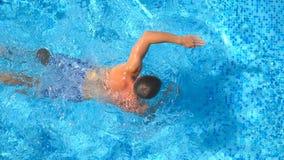 Feche acima da natação do homem novo através da associação que espirra a água claro Indivíduo desportivo que flutua e que aprecia video estoque