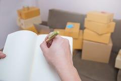 Feche acima da nota da escrita da pena de terra arrendada da mão em um livro Fotografia de Stock Royalty Free