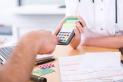 Feche acima da opinião alguém que paga o doutor pelo cartão de crédito fotografia de stock royalty free