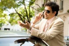 Homem de negócios que inclina-se no carro. fotografia de stock