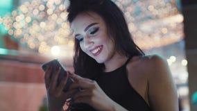 Feche acima da opinião a jovem mulher bonita em uma parte superior preta à moda usando seu telefone celular nas luzes brilhantes  video estoque