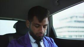 Feche acima da opinião o homem de negócios muçulmano moderno no carro Ele que usa o smartphone vídeos de arquivo