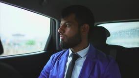Feche acima da opinião o homem muçulmano novo no carro Ele que senta-se no assento traseiro vídeos de arquivo