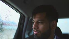 Feche acima da opinião o homem muçulmano novo no carro Ele que senta-se no assento traseiro video estoque