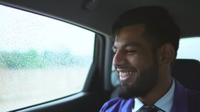 Feche acima da opinião o homem muçulmano novo no carro Ele que senta-se no assento traseiro filme
