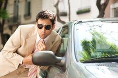 Homem de negócios que prepara no espelho de carro. imagem de stock
