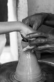 Feche acima da opinião um oleiro mestre que ensina uma criança em como fazer um jarro em uma roda da cerâmica, Chennai, Índia, o  Foto de Stock Royalty Free