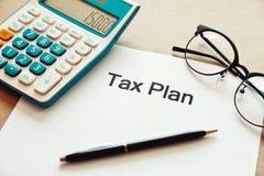 Feche acima da palavra do planeamento fiscal no papel com lugar dos vidros da calculadora, da pena e do olho na tabela de madeira imagens de stock