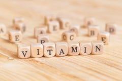 Feche acima da palavra da vitamina feita das letras de madeira na tabela e do A B C D E no fundo da tabela Imagem de Stock Royalty Free