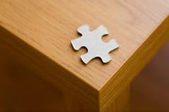 Feche acima da parte do enigma na superfície de madeira Fotografia de Stock Royalty Free