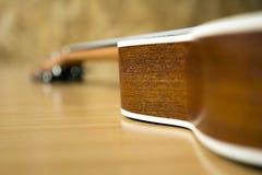 Feche acima da peça da uquelele de madeira no fundo de madeira Fotos de Stock Royalty Free