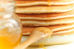 Feche acima da pilha de panqueca com mel de derramamento, a colher de madeira e o frasco do mel Imagem de Stock Royalty Free