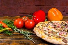 Feche acima da pizza deliciosa, perto são pimentas, dos tomates, ramo o Foto de Stock