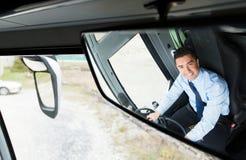 Feche acima da reflexão do motorista no espelho do ônibus Foto de Stock