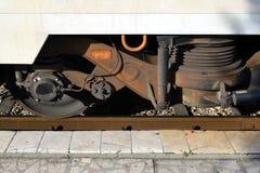 Feche acima da roda e das molas de um automóvel de passageiros em uma plataforma da estrada de ferro foto de stock royalty free