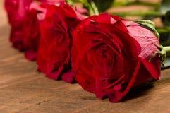 Feche acima da rosa do vermelho na tabela Fotografia de Stock