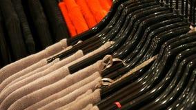 Feche acima da roupa das várias mulheres multi-coloridas que pendura em ganchos pretos da forma em uma loja de roupa na alameda o video estoque