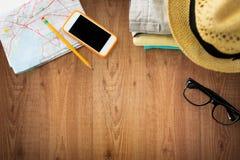 Feche acima da roupa do verão e do mapa do curso na tabela Fotos de Stock
