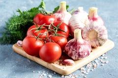 Feche acima da salsa fresca do aneto do alho dos tomates e salgue a placa de madeira Foto de Stock Royalty Free