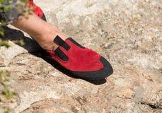 Feche acima da sapata de escalada de borracha vermelha na rocha Fotos de Stock Royalty Free