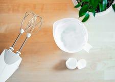 Feche acima da tabela com misturador e dos brancos chicoteados dos ovos para o bolo foto de stock royalty free