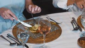 Feche acima da tabela de jantar, mulher que come a salada e o vinho filme