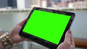 Feche acima da tabuleta verde da tela guardada pela mulher na moda perto da cidade durante o dia filme