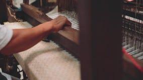 Feche acima da tela de tecelagem do homem usando canelas na máquina do tear vídeos de arquivo