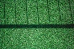 Feche acima da textura da grama artificial ou da grama verde com sombra da cerca do metal na grama no estilo do vintage Foco maci Fotos de Stock
