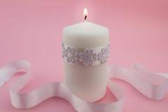 Feche acima da vela branca iluminada isolada no fundo cor-de-rosa Imagem de Stock