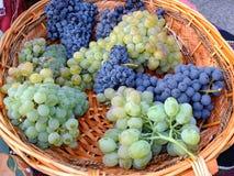 Feche acima da vista da uva para vinho do vermelho e do whitw na cesta de madeira Fotografia de Stock Royalty Free