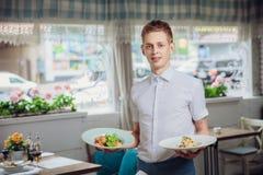 Feche acima da vista de pratos de serviço do garçom no restaurante imagens de stock royalty free