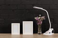feche acima da vista de quadros vazios da foto, de flores no vaso e de candeeiro de mesa Imagens de Stock Royalty Free