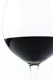 Feche acima da vista de um de vidro transparente completamente do vinho tinto em um fundo branco Foto de Stock Royalty Free
