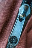 Feche acima da vista de um zíper azul velho em telas vermelhas foto de stock