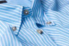 Feche acima da vista de uma camisa azul genérica do negócio com uma linha teste padrão Imagens de Stock Royalty Free