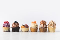 Feche acima da vista de vários queques doces no suporte do bolo foto de stock royalty free