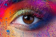 Feche acima da vista do olho fêmea com valor máximo de concentração no trabalho colorido brilhante da forma imagens de stock royalty free
