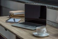feche acima da vista do portátil aberto com tela vazia, xícara de café e caderno imagem de stock royalty free