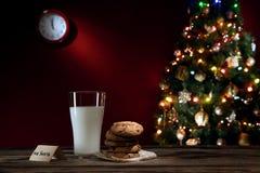 Feche acima da vista do vidro do leite com as cookies na parte traseira da cor Fotografia de Stock