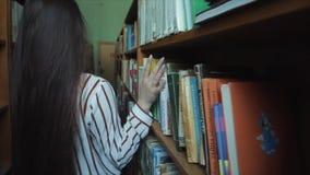 Feche acima da vista esperta das mãos e da moça bonita na camisa e nos vidros brancos na seleção da biblioteca escolar da colagem filme