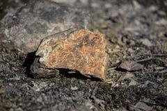 Feche acima da vista exterior da pedra na terra Parte de pedra rochosa alaranjada Textura bonita imagens de stock royalty free