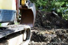 Feche acima da vista lateral da máquina escavadora e da cubeta fotos de stock royalty free