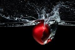 feche acima da vista da maçã vermelha que cai na água imagem de stock